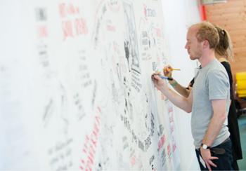 Man drawing visual minutes on a wall