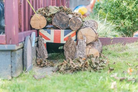 A hedgehog home made with logs and natural materials