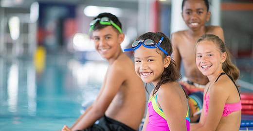 Four children sitting poolside smiling