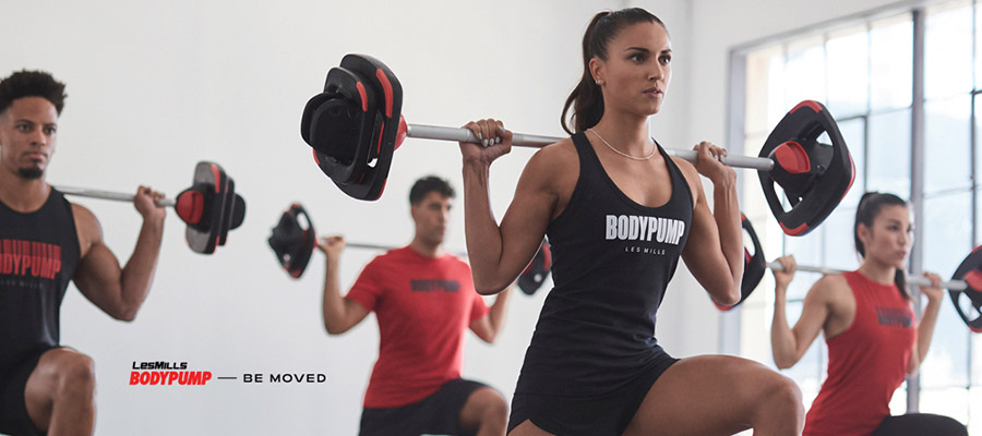 Four people performing a lunge in a Body Pump class