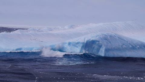 A capsized iceberg in the Weddell Sea, off West Antarctica. Adélie penguins can be seen on the left. (Torsten Albrecht/PIK)