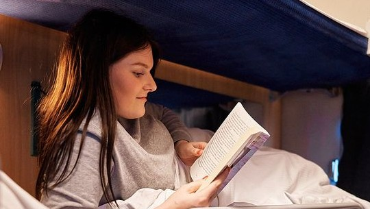 A photo of someone reading a book in bed aboard the sleeper cabin on the Nachtexpress.