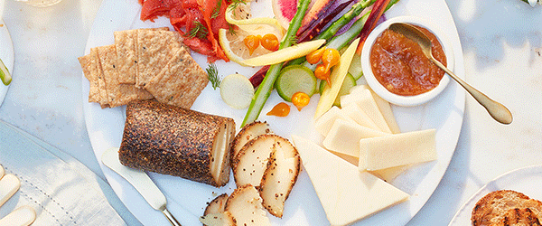Plate of cheese, crackers, vegetables and a compote dip.