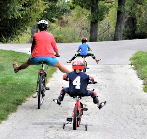 A mother and her two children cycle down an empty road.