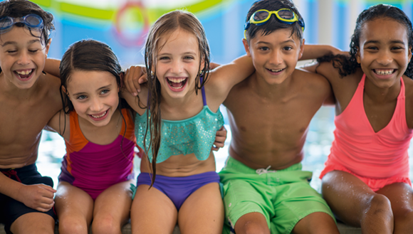 Children sitting on edge of pool