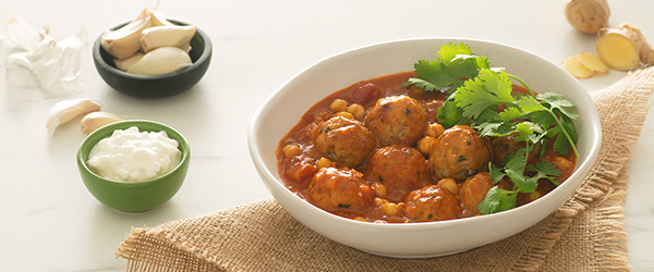 Photo of bowl of turkey meatballs and curry with garlic, ginger, and cottage cheese on the side.