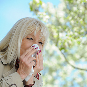 Middle-aged woman blowing her nose into a tissue outdoors.