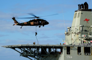 A Black Hawk helicopter hovers over the flight deck to enable Army special operations soldiers to fast-rope onto HMAS Sirius. Defence