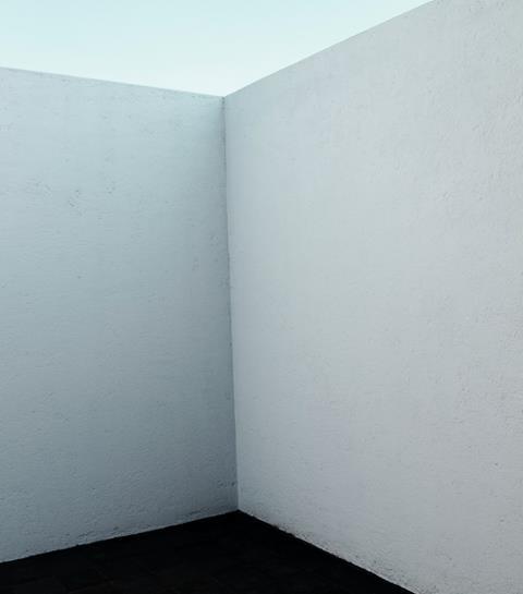 Corner of white wall. Dark floors white ceiling.