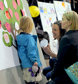A family in Squamish at a consultation pins apple cut-outs on a poster of a tree.