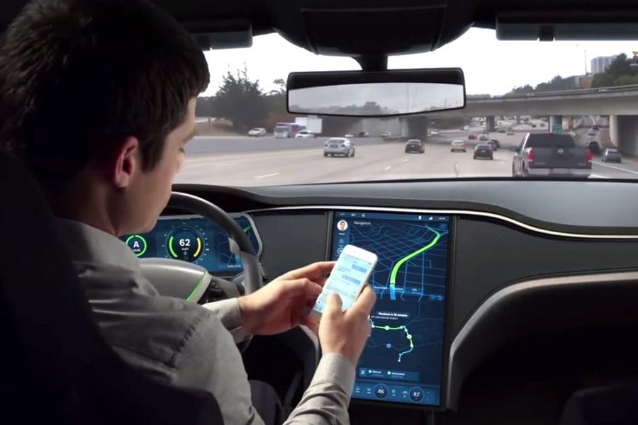A driver uses his mobile phone while in a driverless car, which uses Bosch technology.
