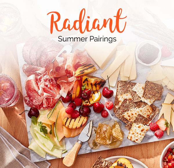 Title – Radiant Summer Pairings. A summer inspired charcuterie board with aged cheddars, slices of salami and prosciutto, crackers, raspberries and cherries.