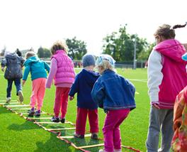 Kids following a physical literacy program by jumping over a flat ladder