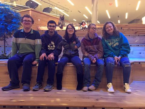 Five college students sitting on a bench at UK, 2 men and 3 women