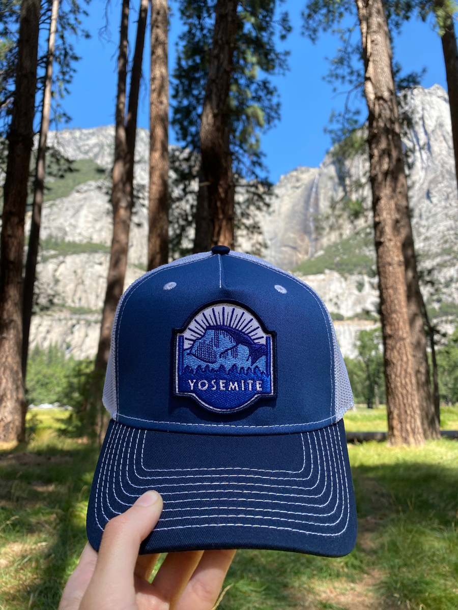 """Our blue Half Dome hat reads """"Yosemite,"""" held up on display in front of a vibrant green meadow and a soaring waterfall."""