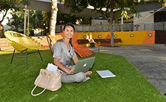 Woman with laptop in courtyard