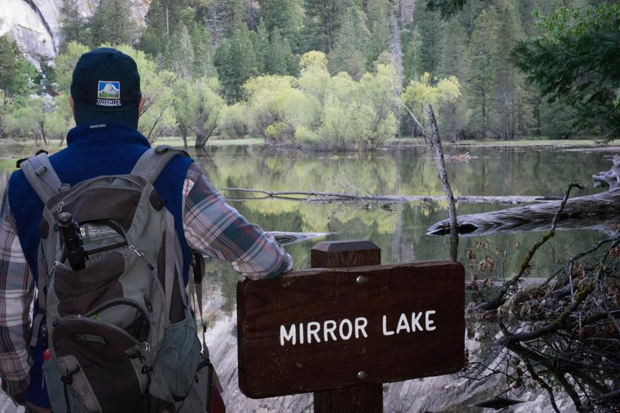 A hiker wearing a Yosemite Conservancy baseball cap poses with the Mirror Lake trail sign, looking out over the pristine, still water.