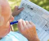Older man completing crossword puzzle in newspaper