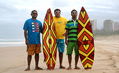 Three men with artistic surfboards