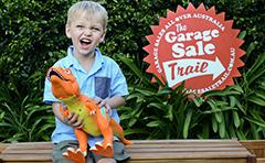 Boy holding toy dinosaur near Garage Sale sign