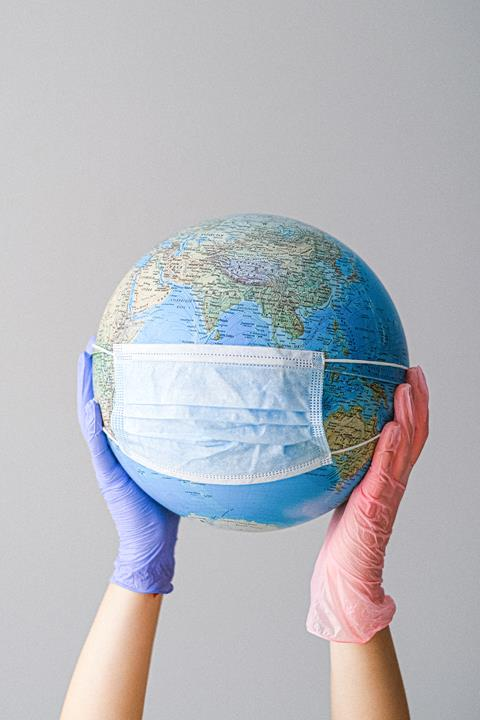 two gloved hands holding a globe with a mask on it