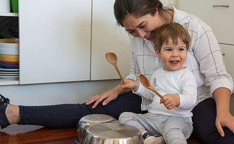Mother and child playing with pots and pans