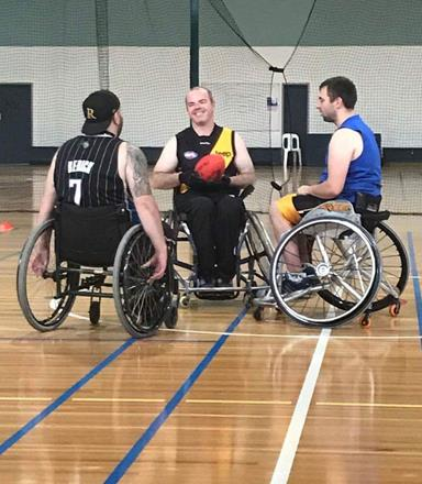 Three men in wheelchairs prepare for the opening throw in a game of AFL Wheelchair.