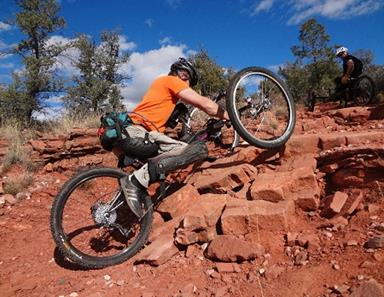 Man riding an off-road handcycle up a steep, rocky path.