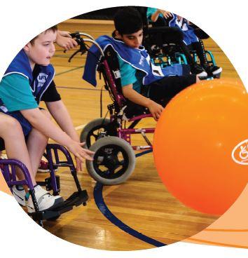 Children in wheelchairs playing balloon football