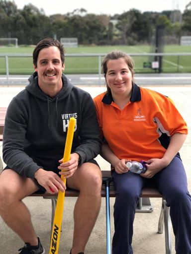 A man and a woman sit on a bench. The man is holding a hockey stick.
