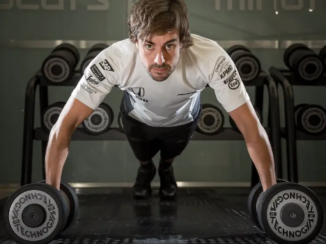 Formula One driver working out with dumbells and staring at the camera