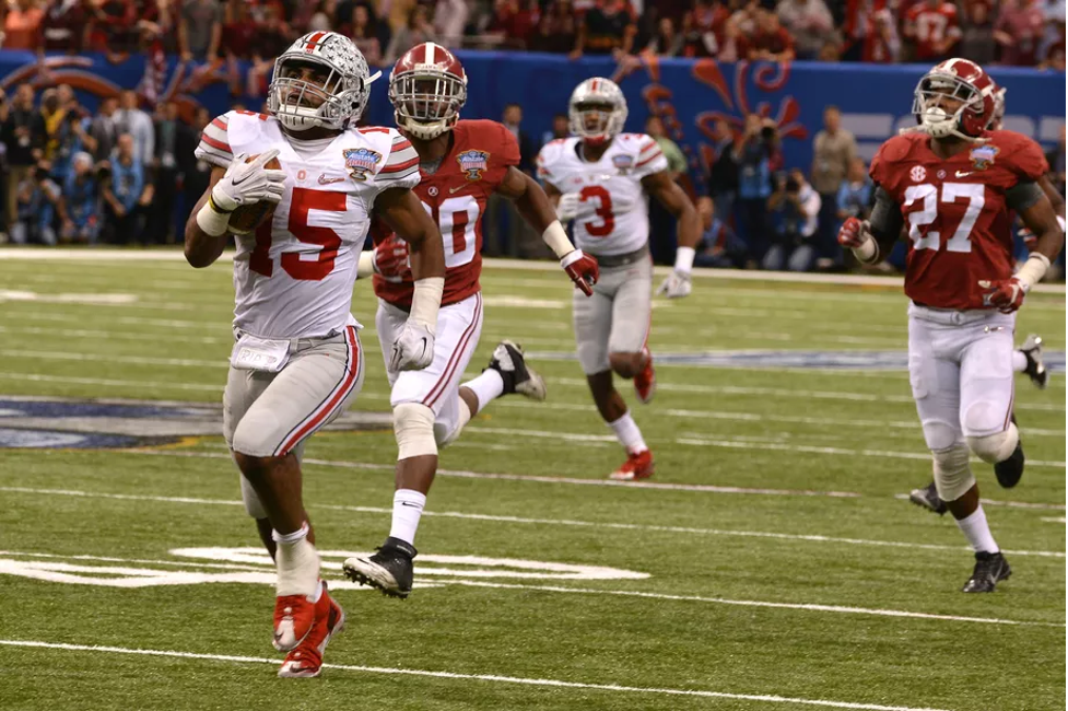 Ohio State football player running to end zone past Alabama football players during college football game