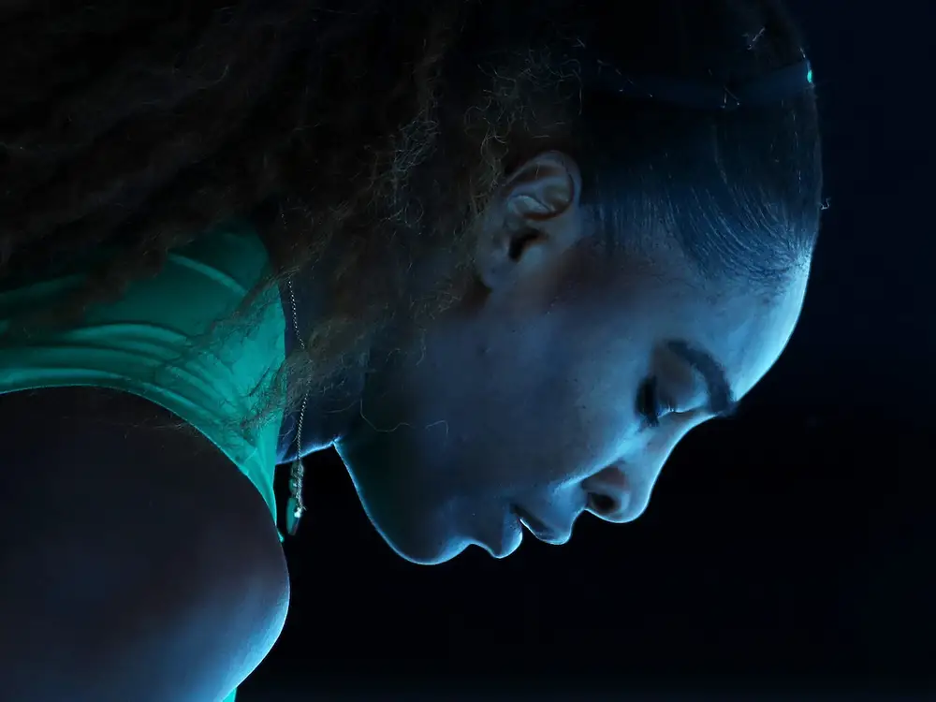 Up close shot of Serena looking down with a dark background