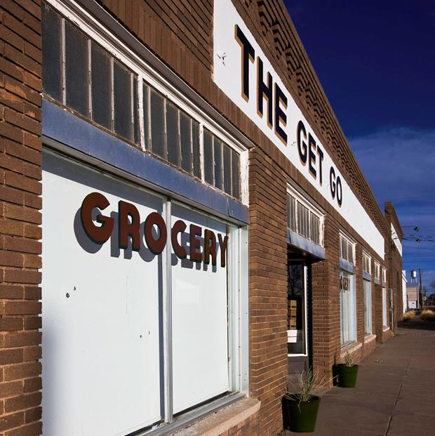 """Exterior of a brick grocery store with """"The Get Go"""" sign"""