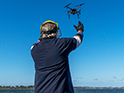 A fisheries officer catching a drone as it lands