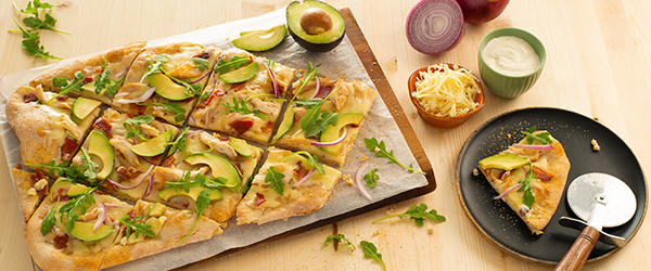 Chicken and avocado on a flat bread pizza with cheese and dip on the side
