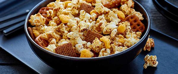 Crunchy cheddar popcorn mix in a bowl.