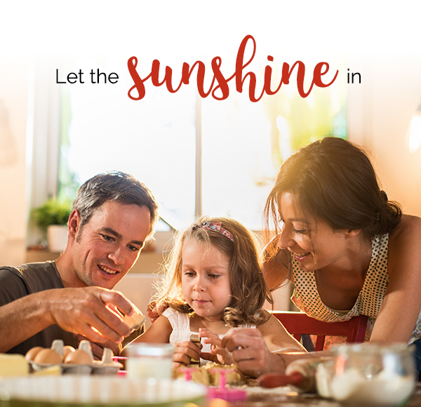 Title - Let the sunshine in. Young girl baking small cakes with her parents in a luminous kitchen.