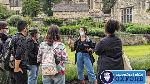Image description: A group of people standing in a garden in front of an Oxford University college. A person with short hair, glasses and jeans is holding a clipboard and speaking to the group.