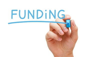 Hand writing word' funding' in blue pen