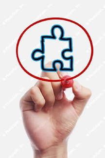 Hand holding a pen drawing a red circle with a blue puzzle piece inside