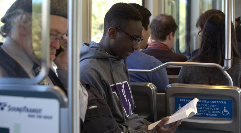 Boy reading a book while sitting on the bus.