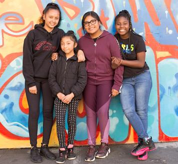 Middle school students in front of a mural