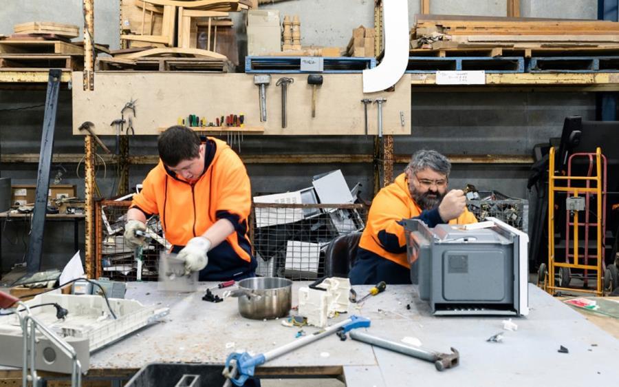 People in hi-vis disassembling e-waste