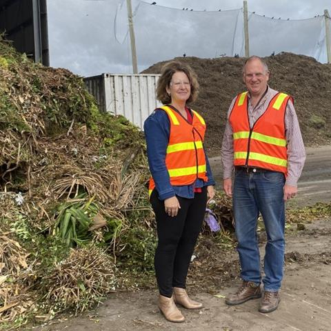 People standing in front of a pile of green waste