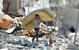 A Palestinian searches through rubble of his destroyed home. Photo: UN Photo | Shareef Sarhan